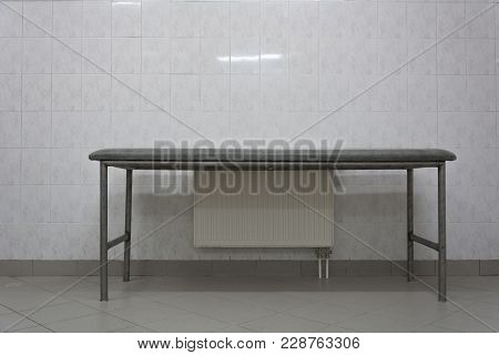 Metal Massage Table Near The Battery On A White Wall Background