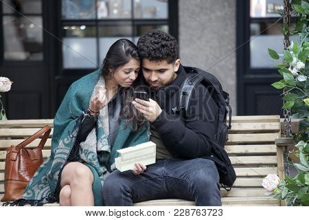 London, England - September 11, 2017 Happy Couples Look In The Phones, Sitting On A Bench Near Coven