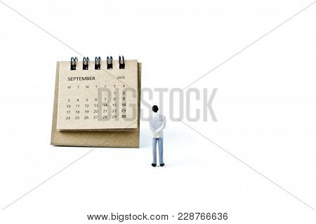 September. Two Thousand Eighteen Year Calendar And Miniature Plastic Man On White Background.