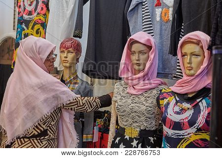 Kashan, Iran - April 25, 2017: Elderly Iranian Woman In A Clothing Store Are Looking At Dummies In P