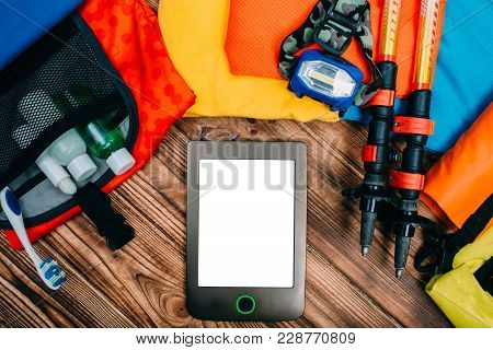 Top View Journey And Travel Preparations Concept With Ebook On Wooden Table With Empty Space In The