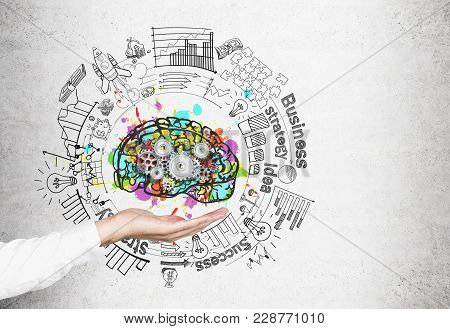 Hand Of An Unrecognizable Businessman Holding A Colorful Brain Sketch With Cogs On It And A Business