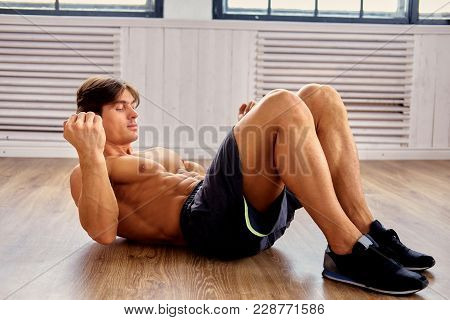 Suntanned Muscular Shirtless Male Doing Stomach Workouts On A Floor In A Room.