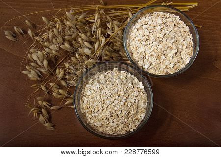 Oat Ears Stems And Oat Flakes In A Bowl On A Dark Brown Wood Background. Top View. Oat Flakes Big An