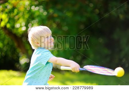 Little Boy During Tennis Training Or Workout. Preschooler Playing Badminton In Summer Park. Child Wi