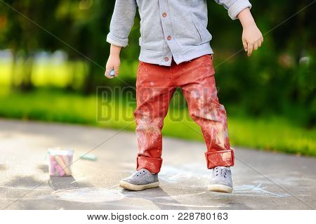 Close-up Photo Of Little Kid Boy Drawing With Colored Chalk On Asphalt. Creative Leisure For Toddler