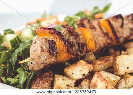 Pork Kebab Skewer Dish With Potatoes And Salad