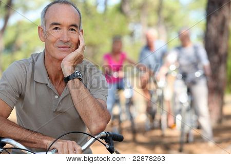 Senior on a bike with friends in the background
