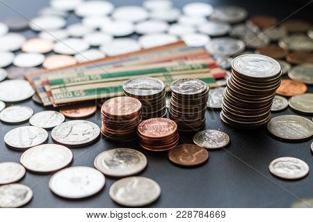 Stacked Us Coins Surrounded By Coins And Paper Rolls