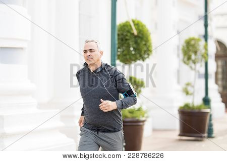 Fit Middle Aged Hispanic Man Jogging Outdoors In The City