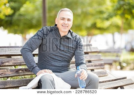 Good Looking Middle Aged Man Sitting On A Park Bench With A Water Bottle After Exercise Session