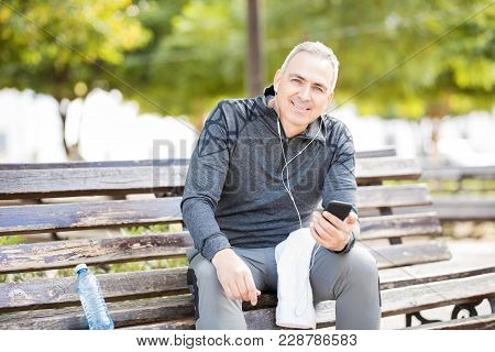 Portrait Of Good Looking Mature Man  Listening To Music With A Smartphone While Taking A Break From