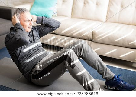 Active And Fit Mature Man Doing Crunches In The Living Room At Home