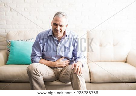 Old Man Feeling Unwell With A Stomach Ache While Sitting On A Sofa At Home