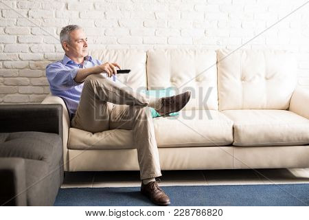 Middle Aged Man Sitting On Sofa Changing The Channels Of Television With Remote Control While Watchi