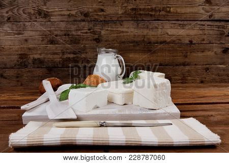 dairy food fresh white greek goat sheep feta cheese on plate with milk in pitcher cherry tomatoes french bun over dark wooden table