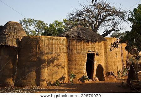a traditional mud house in a west african village poster
