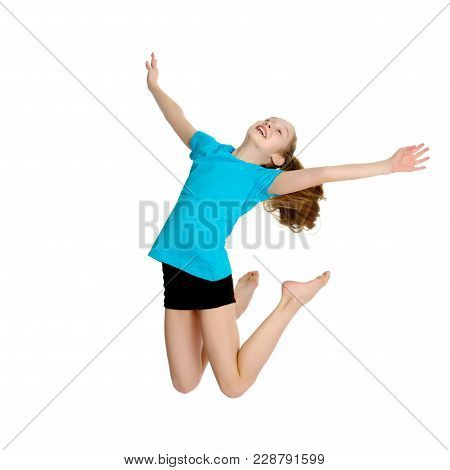 A Little Girl Gymnast Joyfully Jumps And Wags Her Hands. The Concept Of Sport And Fitness. Isolated