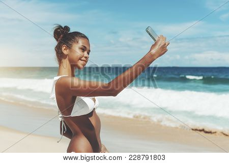 Young Sexy Brazilian Model Girl Is Taking Selfie While Standing On The Ocean Beach After Swimming; B