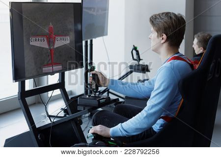 ST. PETERSBURG, RUSSIA - FEBRUARY 22, 2018: Gamers in the flight simulator zone during St. Petersburg Cyber-Sport Festival. Main event of the festival is Counter-Strike: Global Offensive tournament