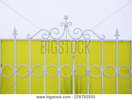 Figured White Metal Fence On A Yellow Background.