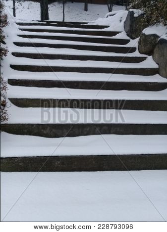Snow Covered Stair Steps Without Handrails For Pedestrians With Rocks And Stones On Sides