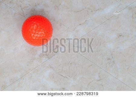 Orange Golf Ball On Marble Tiles. Background