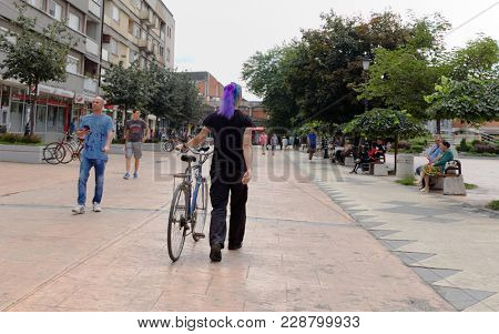 PIROT, SERBIA - JULY 27, 2017: a man with purple hair crosses the pedestrian area in the center of the town