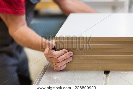 production, manufacture and woodworking industry concept - close up of senior worker or carpenter with fibreboards at furniture factory workshop