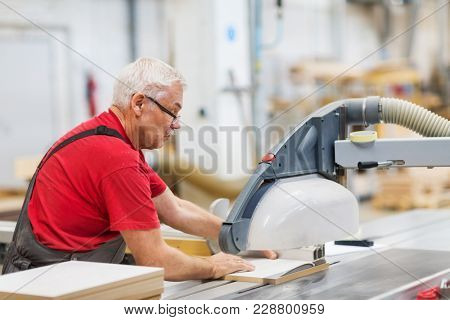 production, manufacture and woodworking industry concept - carpenter working with sliding panel saw and sawing fibreboard at furniture factory workshop