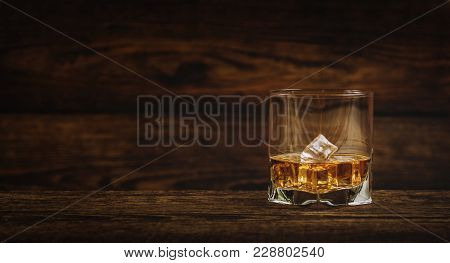 Whisky Or Whiskey Or Bourbon With Ice On Wood Background
