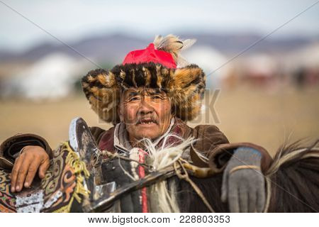 OLGIY, MONGOLIA - SEP 30, 2017: Eagle Hunter at traditional clothing, with a golden eagle on his arm during annual national competition with birds of prey BERKUTCHI of West Mongolia.
