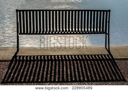Back Of An Empty Metal Bench By A Reflective Lake With Sun On Water And Shadow Behind Bench
