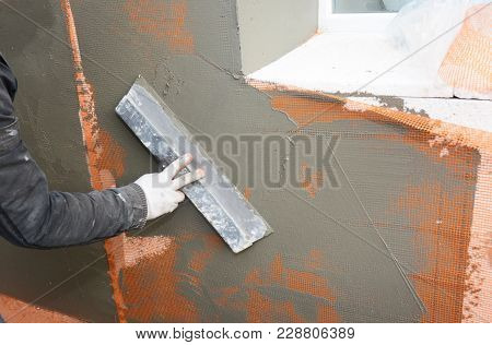Man Hands  Plastering, Stucco Wall Styrofoam Or Foam Board Insulation. Styrofoam Insulation For Hous