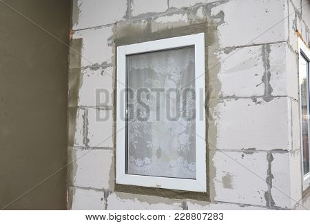 Unfinished house plastering wall with fiberglass mesh, plaster mesh, rigid foam insulation, stucco, window insulation. poster