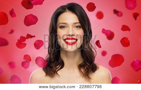 beauty, valentines day, make up and people concept - happy smiling young woman with red lipstick over rose petals on background