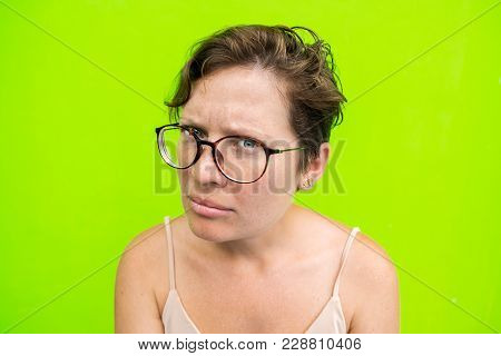 Portrait Of A Woman In Glasses With A Look At The Camera And An Unhappy Face. Question And Disconten