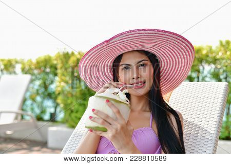 Swimsuit Concept. Beautiful Girls In Swimwear Are Drinking. Asian Girls Drink Fruit Juice At The Poo