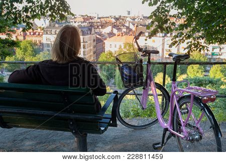 Stockholm, Sweden, June 2013:Woman stops for rest with her bicycle in Stockholm City