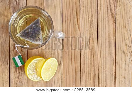 Triangular Tea Bag In A Glass And A Slice Of Lemon On A Wooden Surface