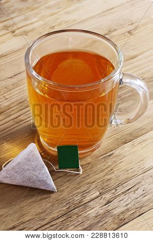 A Glass Of Black Tea With A Triangular Tea Bag On A Wooden Surface