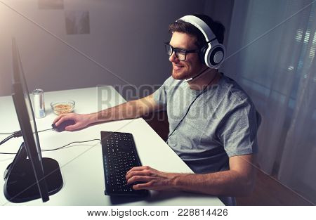 technology, gaming, entertainment, let's play and people concept - happy young man in headset and glasses with pc computer playing game at home and streaming playthrough or walkthrough video