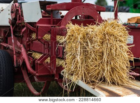 Old But Working Straw Baler Pushing Out A Fresh Bale Of Straw.