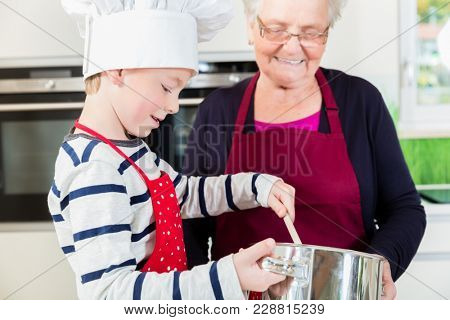 Granny and little boy preparing together food in kitchen