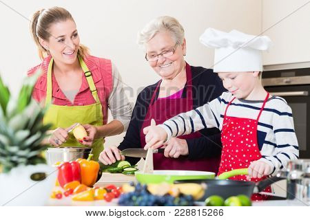 Granny, mum and son talking while cooking together in kitchen