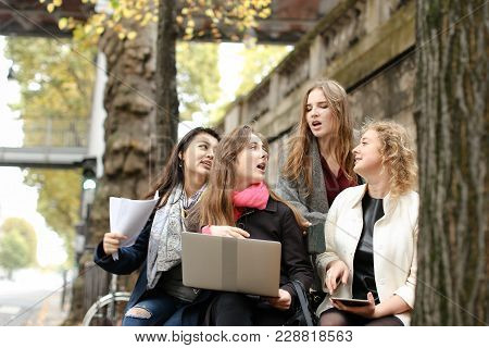 Hardworking Girls Learning New Subject With Laptop And Papers On Bench Near Traffic Light. Concept O