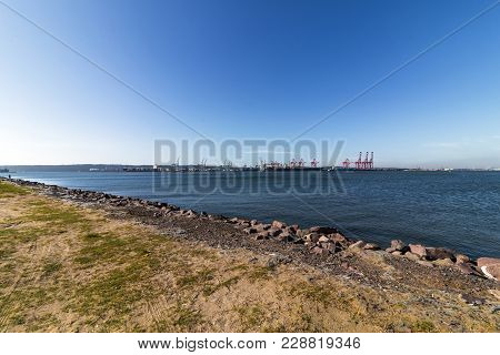 Sand Water Ripples Ships And Cranes Against Blue Sky