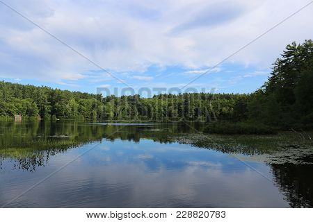 A Lake In New Hampshire Reflecting The Tree Line And Sky.