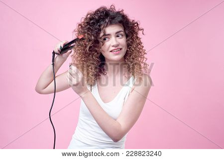 Beautiful Woman With Amazing Curls In White Shirt Holds Styling Accessories In Hand. Top View. Hair