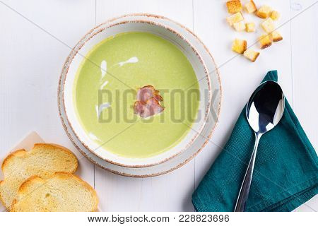 Green Pea Cream Soup With Bacon And Cream In Bowl With Croutons On White Wooden Table. Light Summer
